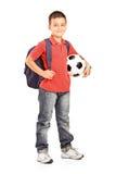 Kind mit dem Rucksack, der eine Kugel anhält Lizenzfreies Stockbild