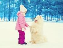 Kind mit dem weißen Samoyedhund, der auf Schneewinter spielt Lizenzfreie Stockfotografie