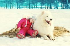 Kind mit dem weißen Samoyedhund, der Spaß auf Schnee im Winter hat Lizenzfreies Stockfoto