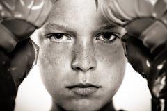 Kind mit den Boxhandschuhen, die auf Stanzplatte sich konzentrieren Stockfotos