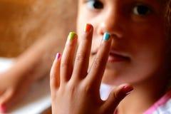 Kind mit den gemalten Fingernägeln Stockfotos