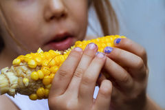 Kind mit den schmutzigen Händen Maiskörner essend lizenzfreies stockfoto