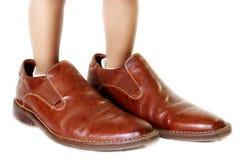Kind mit den Schuhen des Vatis Lizenzfreie Stockfotografie