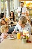 Kind mit der Großmutter am Kaffee Kuchen essend lizenzfreie stockbilder