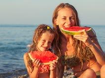 Kind mit der Mutter, die Wassermelone isst Lizenzfreies Stockfoto