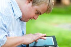 Kind mit Down-Syndrom, das auf Tablette spielt. Stockfotos