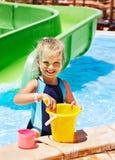 Kind mit Eimer im Swimmingpool. Stockbild