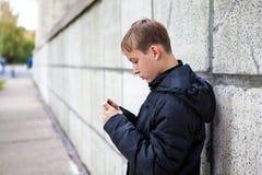 Kind mit einem Telefon lizenzfreie stockfotografie