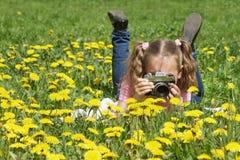 Kind mit einer Kamera im Löwenzahn Stockfotografie