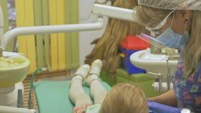 Kind mit einer Mutter an einer Zahnarzt ` s Aufnahme Das Mädchen liegt im Stuhl, hinter ihrer Mutter Der Doktor arbeitet mit stock video footage