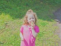 Kind mit Eiscreme geht in der Hand in den Park Lizenzfreie Stockfotografie