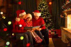 Kind mit Eltern las die Geschichten, die auf Trainer vor Kamin in Weihnachten verziertem Hausinnenraum sitzen Lizenzfreie Stockfotografie