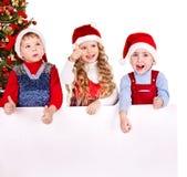 Kind mit Fahne nahe Weihnachtsbaum. Stockbild