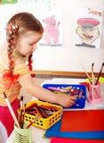 Kind mit Farbenbleistift im Spielraum. stockfotografie