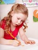 Kind mit Farbenbleistiftabgehobenem betrag im Vortraining. Lizenzfreie Stockfotografie