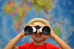 Kind mit Ferngläsern schaut herum Abenteuer- und Reisekonzept Kreativer Hintergrund Junge spielt in Kapitän Lizenzfreie Stockfotos