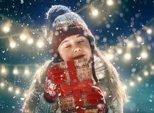 Kind mit Geschenk auf dunklem Hintergrund stockfotos