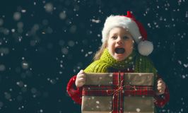Kind mit Geschenkbox auf dunklem Hintergrund lizenzfreie stockbilder