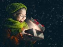Kind mit Geschenkbox auf dunklem Hintergrund lizenzfreie stockfotos