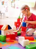 Kind mit gesetztem Bau des Blockes und des Aufbaus. Stockfotografie