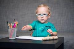 Kind mit Gläsern sitzt an einem Tisch auf dem Hintergrund der Tabelle für einen Sehtest Lizenzfreies Stockfoto