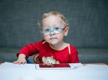 Kind mit Gläsern sitzt an einem Tisch auf dem Hintergrund der Tabelle für einen Sehtest Lizenzfreie Stockfotos