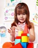 Kind mit hölzernem Block im Spielraum. Stockfoto