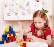 Kind mit hölzernem Block im Spielraum. Stockbild