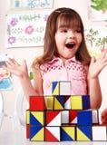 Kind mit hölzernem Block im Spielraum. Lizenzfreie Stockfotos