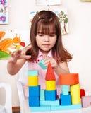 Kind mit hölzernem Block im Spielraum. Lizenzfreie Stockfotografie