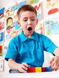 Kind mit hölzernem Block im Spielraum. Lizenzfreies Stockfoto