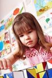 Kind mit hölzernem Block im Spielraum. Stockfotos