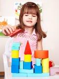 Kind mit hölzernem Block im Spielraum. Stockfotografie