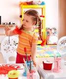 Kind mit Lack und Pinsel im Spielzimmer. Lizenzfreie Stockfotos