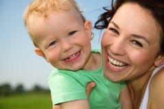 Kind mit Mutterspiel draußen Stockbilder