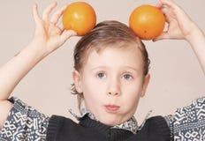 Kind mit Orangen Stockfoto