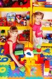 Kind mit Puzzlespiel, Block im Spielraum. Lizenzfreie Stockbilder