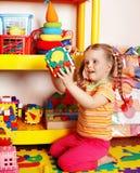 Kind mit Puzzlespiel und Block im Spielzimmer. Stockbild