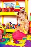 Kind mit Puzzlespiel und Block im Spielzimmer. Lizenzfreie Stockbilder