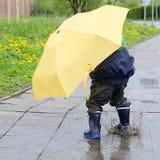 Kind mit Regenschirm in der Pfütze Stockbilder