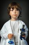 Kind mit Retorte und Mikroskop lizenzfreie stockfotos