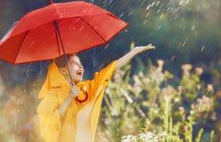 Kind mit rotem Regenschirm Stockbild