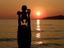 Kind mit Schätzchen spielt im Sonnenuntergang auf Meer lizenzfreie stockbilder