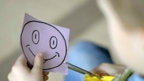 Kind mit Scheren schneidet vom Papiersmiley stock footage