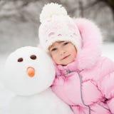 Kind mit Schneemann Stockbilder