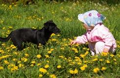 Kind mit schwarzem Hund Lizenzfreie Stockbilder