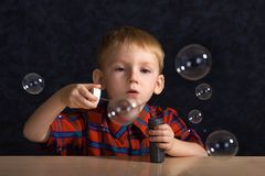 Kind mit Seifenluftblasen Stockfotos