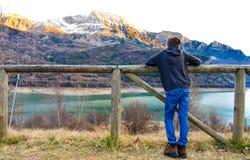 Kind mit seinen Armen auf einem Bretterzaun, den Schnee auf den Spitzen der Berge und des blauen Wassers des Sees in beobachtend lizenzfreie stockbilder