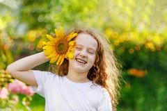 Kind mit Sonnenblumen in seinen weißen Zähnen der Handshow lizenzfreies stockbild