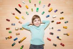 Kind mit Spielzeugautos um ihn lizenzfreies stockbild